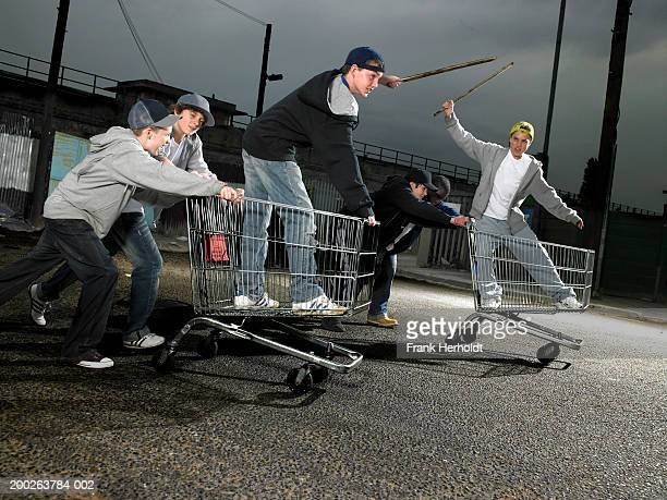 group of teenage boys (13-15) racing with shopping trolleys - chav stock photos and pictures