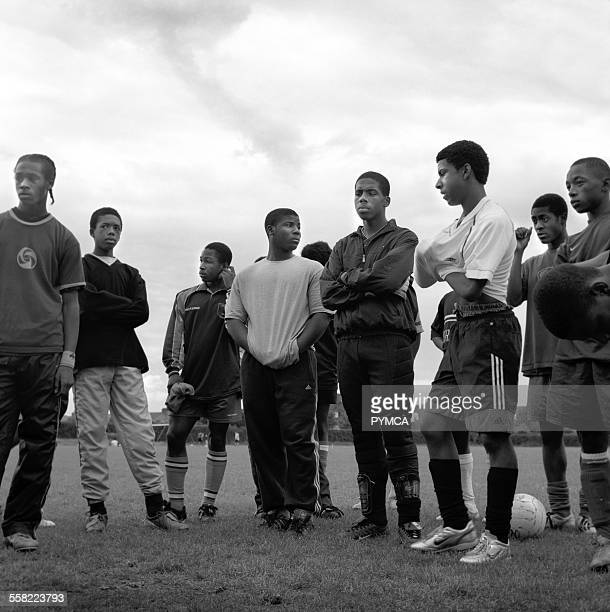 A group of teenage boys taking a break from playing league football at the Broadwater Farm pitches in Tottenham London 2005