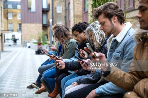 group of teenage friend focused on their own smartphone texting on social media - enslaved stock pictures, royalty-free photos & images