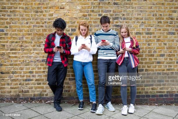 gruppe von teenager-freund konzentrierte sich auf ihre eigenen smartphone sms auf social media - generation z stock-fotos und bilder
