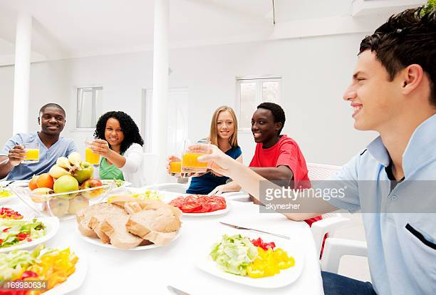 Group of teenage friends having dinner outdoors.