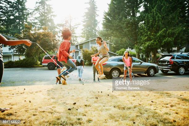 Group of teenage friends jumping rope together in front yard on summer evening