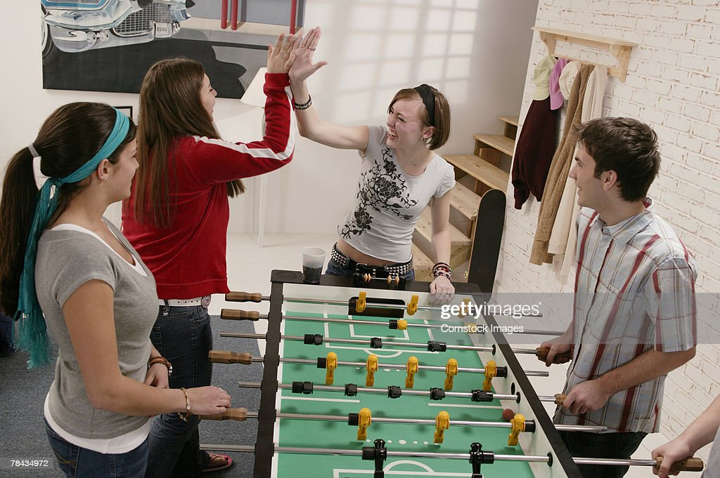 Group of teenage friends playing table soccer : Stockfoto