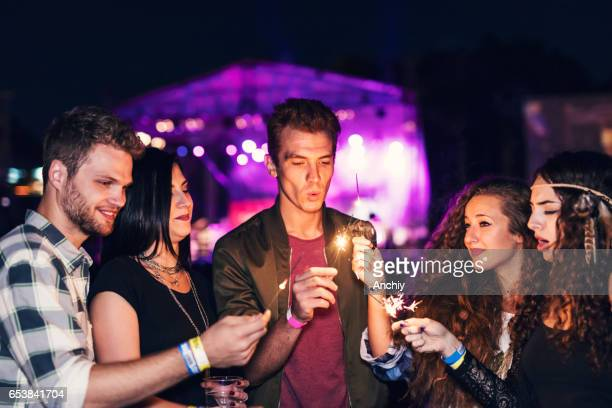 Group of teenage friends playing with sparklers at the music festival