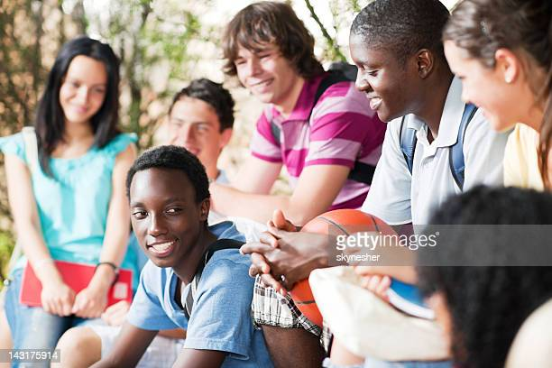 Group of teenage friends sitting on the bench.