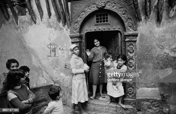 A group of teenage girls appear in a street doorway watched by teenage boys in the Casbah of Algiers
