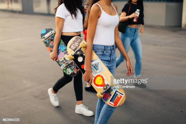 Group of teenage girls carrying skateboards