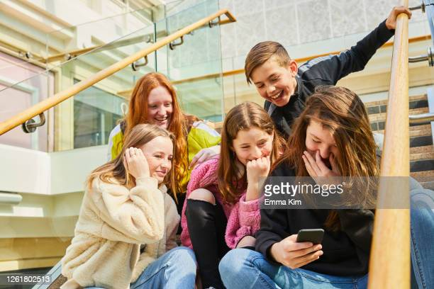 group of teenage girls in a shopping mall, checking their mobile phones. - examining stock pictures, royalty-free photos & images