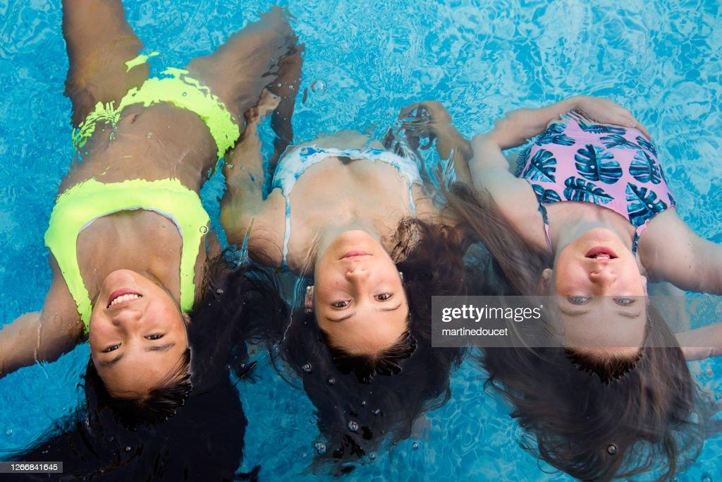Group of teenage girls in pool playing mermaids. : Stock Photo