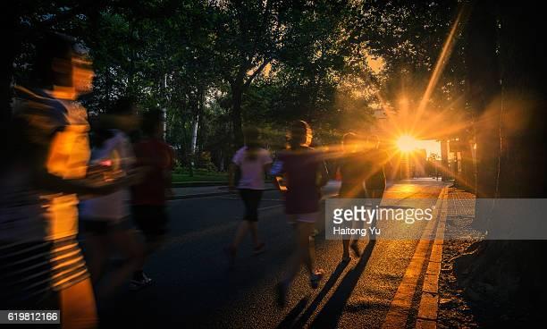 Group of teenage girls jogging past at dawn