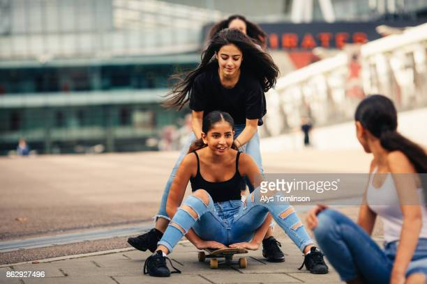 Group of teenage girls playing on skatebaord