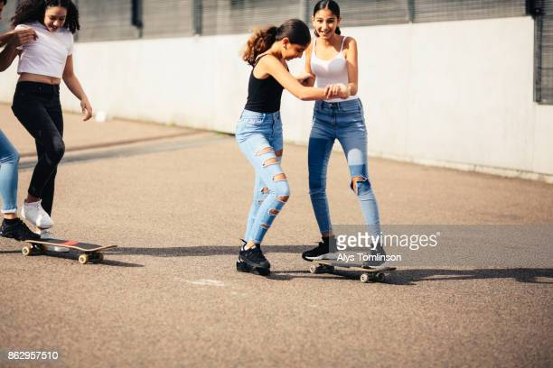group of teenage girls playing on skateboards - doing a favor stock pictures, royalty-free photos & images