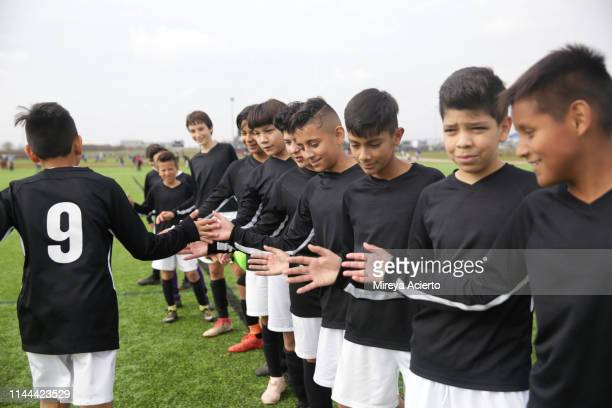 A group of teenage Latino soccer players congratulate their teammate on an outdoor soccer field.