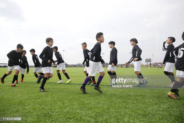 A group of teenage Latino soccer players do drills in their team uniforms on an outdoor soccer field.