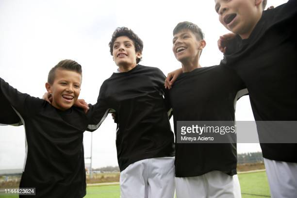 A group of teenage Latino soccer players wearing team uniforms, laugh while huddled in a group together.