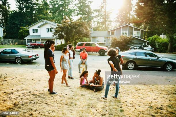 Group of teenage neighborhood friends hanging out in front yard on summer evening