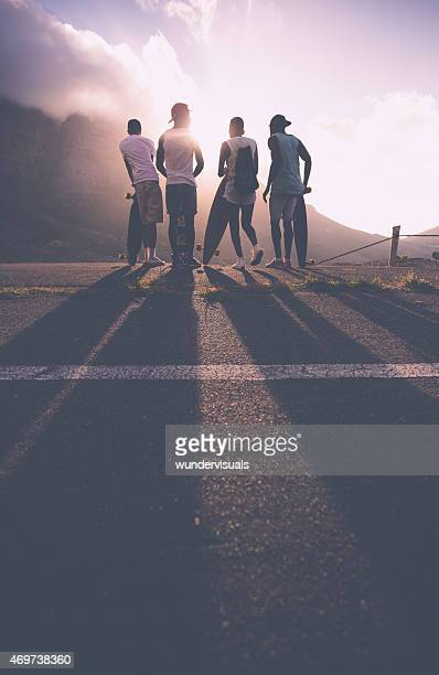 Group of teenage skater friends at sunset
