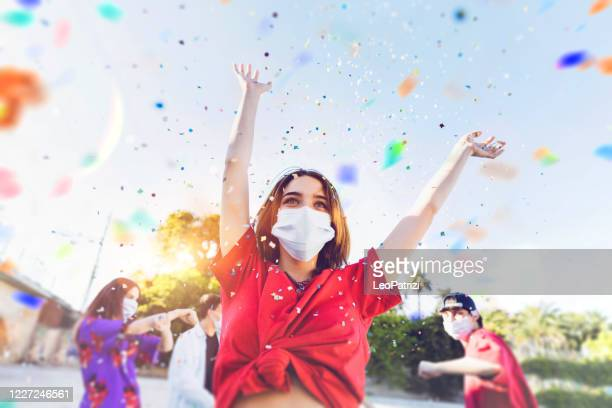 group of teenagers celebrating at a party wearing face masks - celebration stock pictures, royalty-free photos & images
