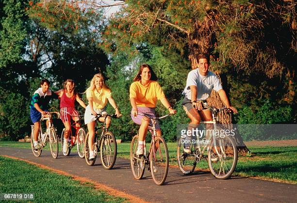 Group of teenagers (16-18) cycling on path in park