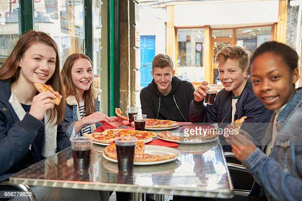Group Of Teenagers Eating Pizza In Cafe