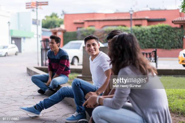 group of teenagers haning out on street curb - henry street stock pictures, royalty-free photos & images