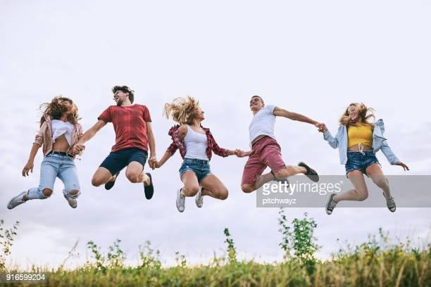 Gruppe von Jugendlichen Hand in Hand und springen