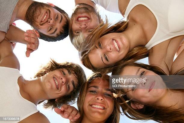 Groupe d'adolescents en cercle avec leur têtes ensemble souriant