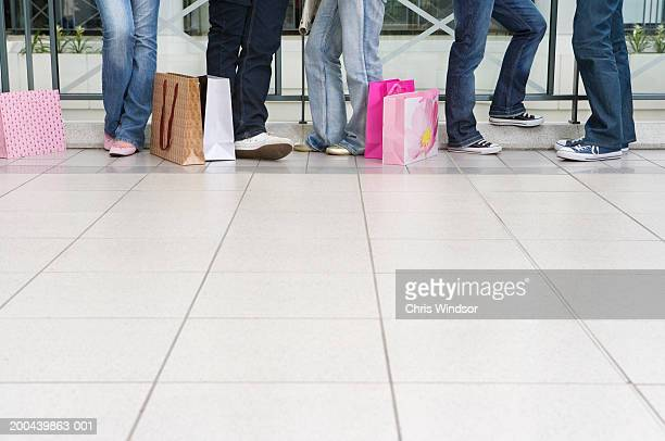 Group of teenagers (15-17) in shopping centre with bags, low section