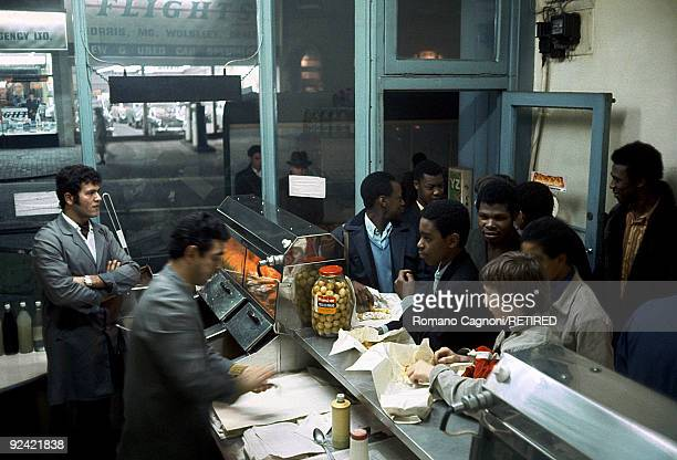 A group of West Indian immigrants join the queue at a fish chip shop in Handsworth Birmingham circa 1978