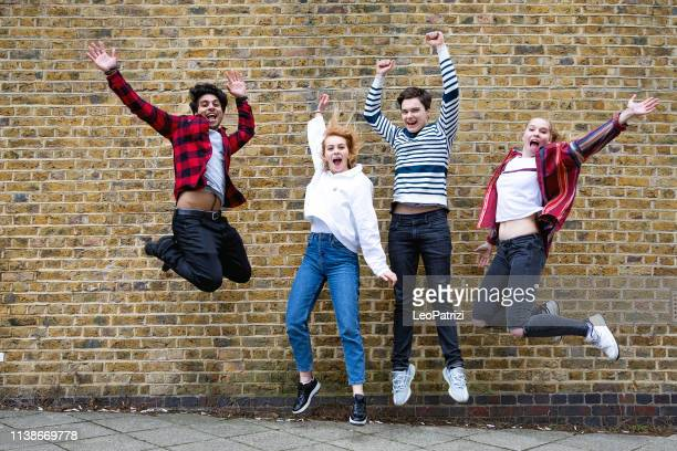 group of teenagers jumping agains a brick wall - 18 19 years stock pictures, royalty-free photos & images