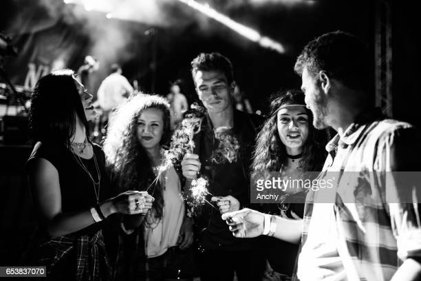 Group of teenagers lights sparklers at the pop music concert. black and white photo
