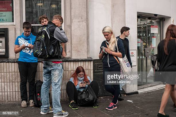 Group of teenagers most of them looking at their cellphones London England 17th September 2014