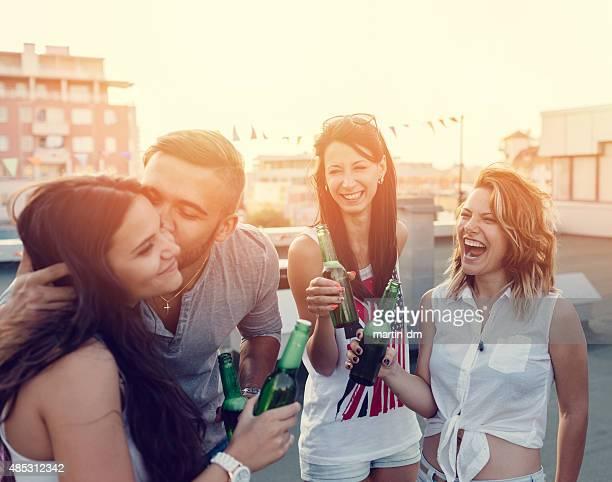 Gruppe von Teenagern, die auf einer party auf dem Dach