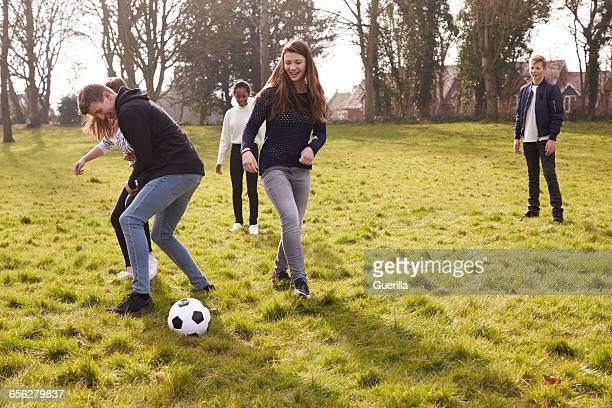 Group Of Teenagers Playing Soccer In Park Together