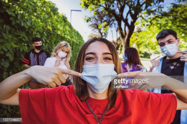 group of teenagers posing showing their protective face masks - adolescence stock pictures, royalty-free photos & images
