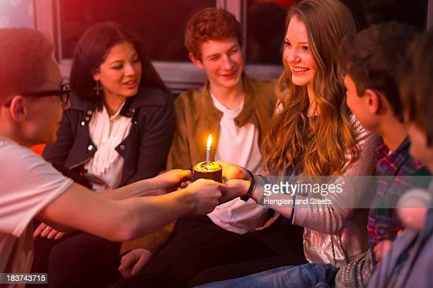 Group of teenagers sitting around birthday cake