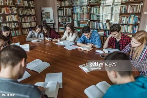 Gruppe von Jugendlichen sitzen um den Tisch in einer Bibliothek und Bücher zu lesen.