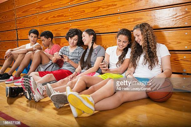 Group of teenagers (16-17) sitting on floor in gym and using smart phones