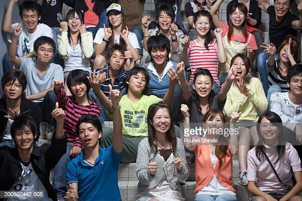 group of teenagers (13-18) sitting on steps, cheering - cheering ストックフォトと画像