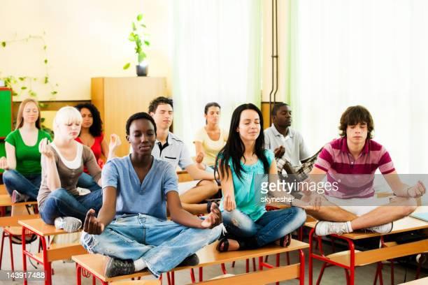 Grupo de adolescentes sentado en el escritorio en la posición del loto.