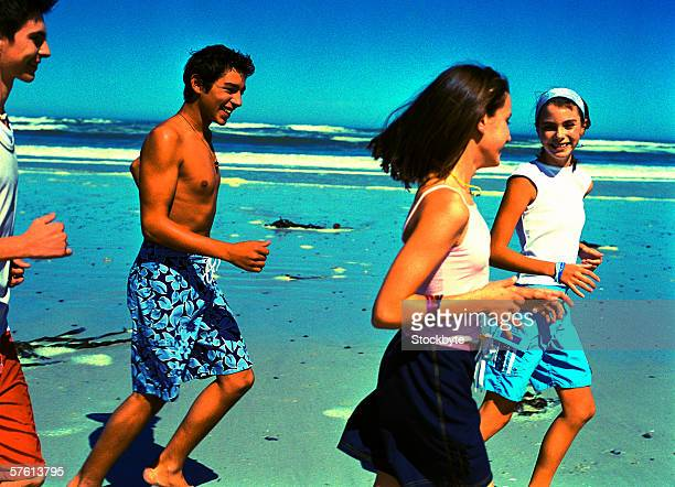 Group of teenagers (14-18) smiling running at the beach