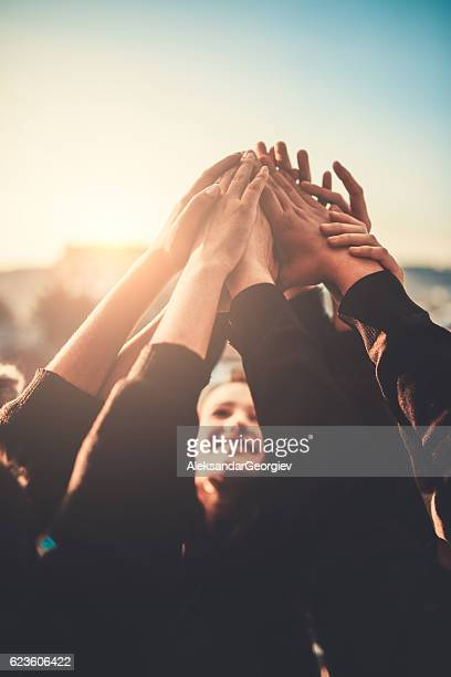 group of teenagers volunteer with raised hands to the sky - comemoração conceito imagens e fotografias de stock