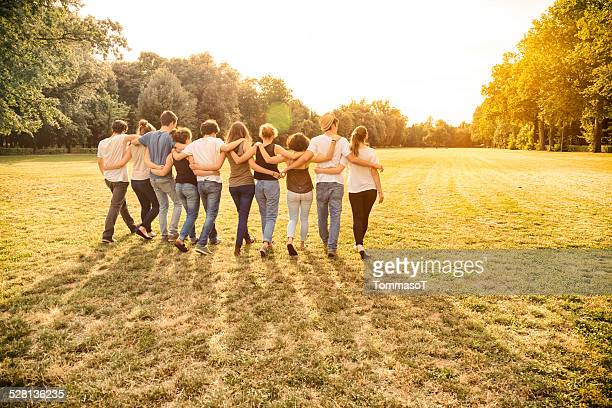 Group of teenagers walking in a field holding together