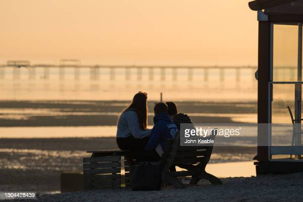 Group of teenagers watch the sunset over the pier as parts of the UK enjoyed warm weather on February 27, 2021 in Southend on Sea, United Kingdom....