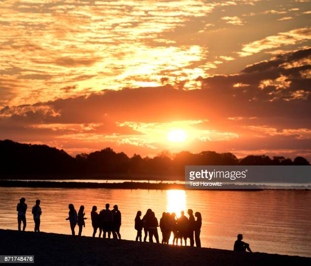 group of teenagers watching sunrise at beach. - westport connecticut stock photos and pictures