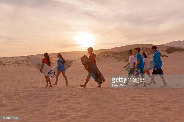 Group of teenagers (16-17) with surfboards on beach, Tarifa, Costa de la Luz, Cadiz, Andalusia, Spain