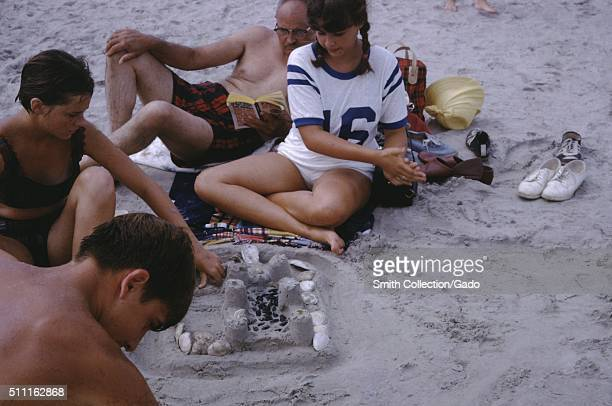 Group of teenagers with their father wearing swimwear relaxing on a sand beach and building a sand castle with rocks and shells 1960