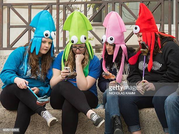 A group of teens look at one of their friend's smartphones as they sit outside the Natural History Museum in Washington on April 8 2015 A Pew...