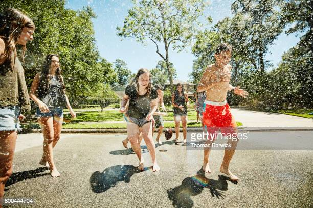 Group of teens playing in spray from fire hydrant on sunny summer afternoon