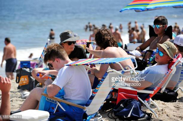 A group of teens sunbathes at Hampton Beach in Hampton New Hampshire on August 5 as COVID19 cases in New England are on the rise Hampton Beach is...